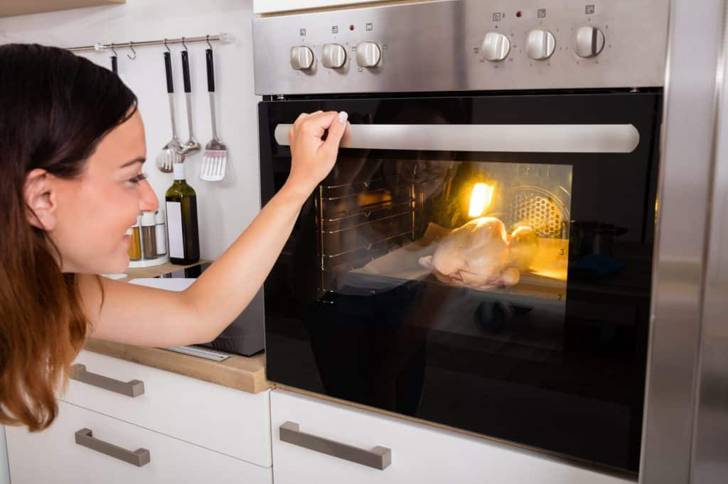 young woman checking oven