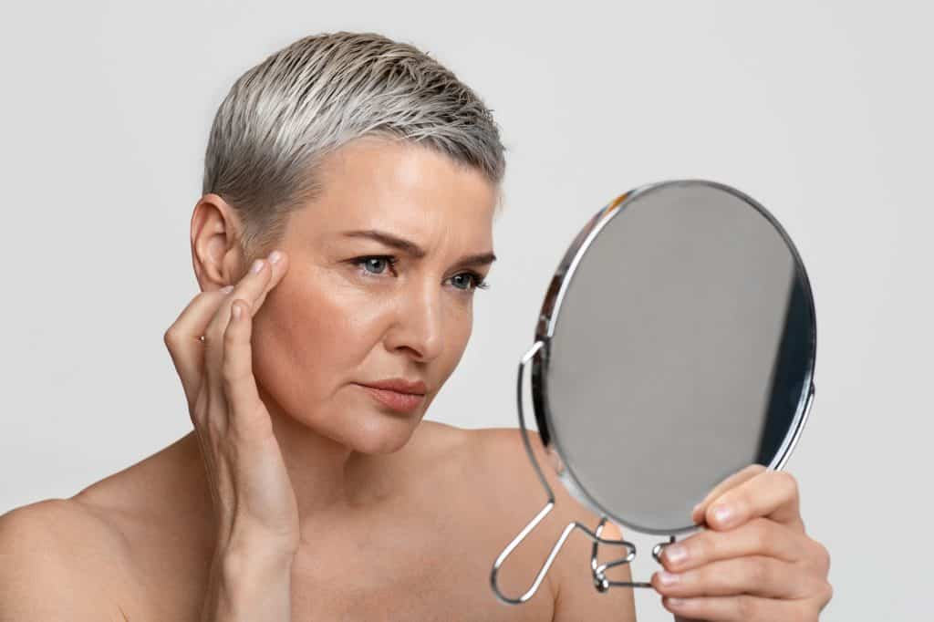 mature lady checking her eye wrinkles in the mirror