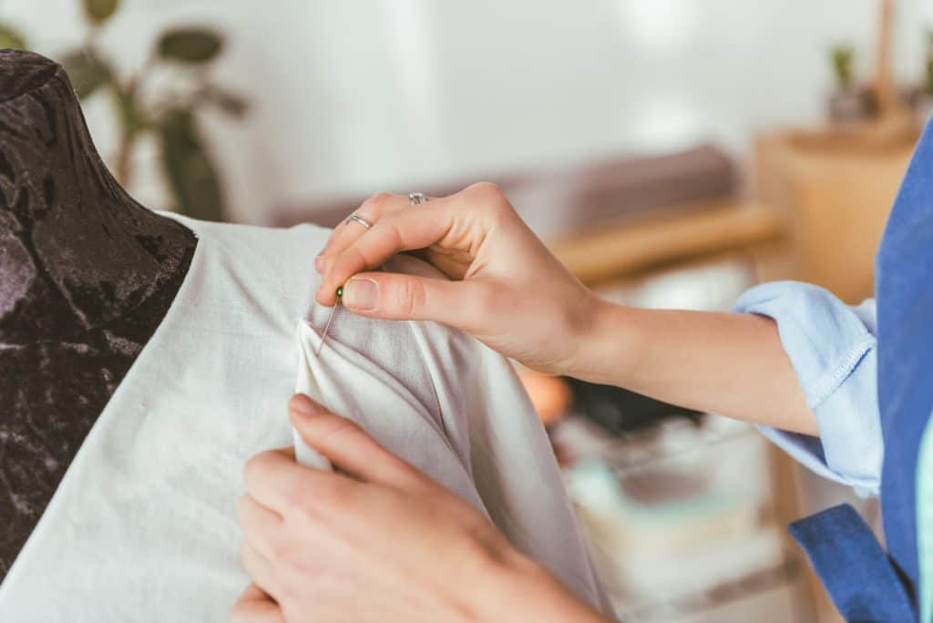 Woman pinning fabric to a dressmaking dummy