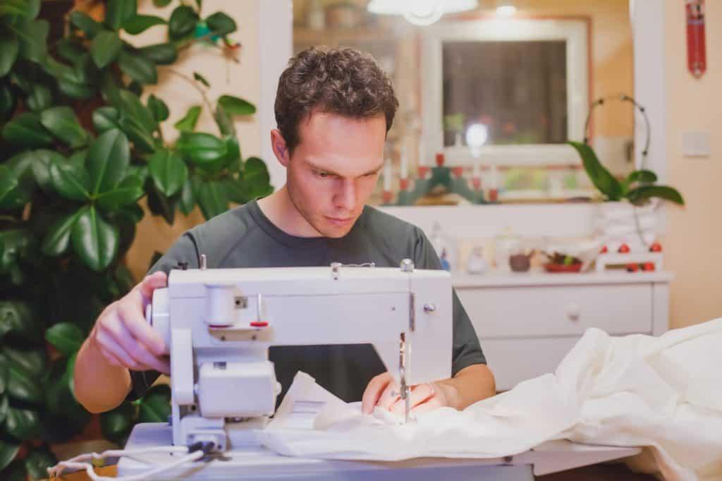 man sewing fabric on a machine
