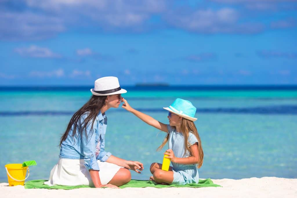 a little girl applying sunscreen to her mother's face on a beach