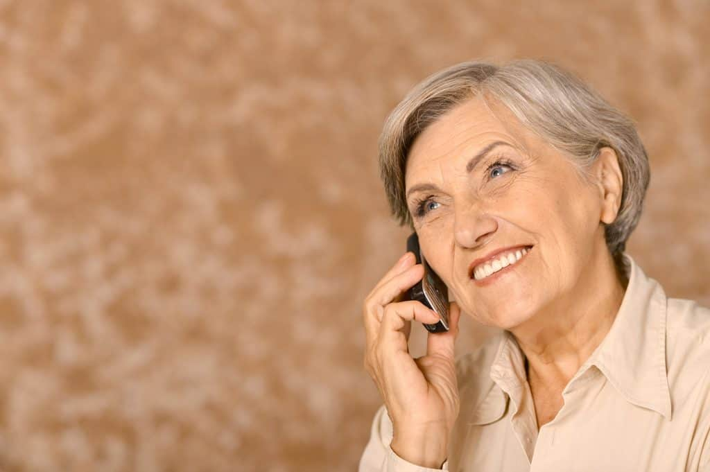 elderly lady smiling and talking on the phone
