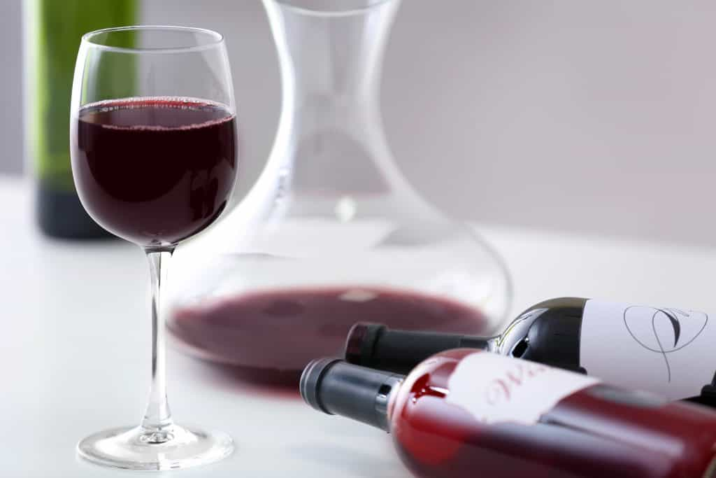 red wine bottles with a decanter and wine glasses