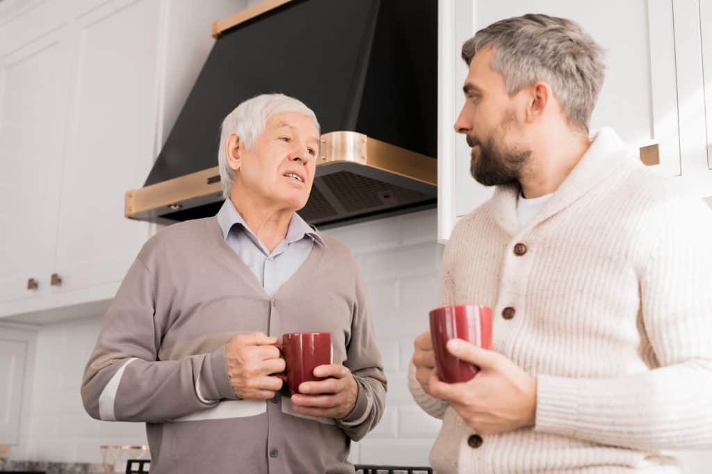 son talking to elderly father over a cup of tea