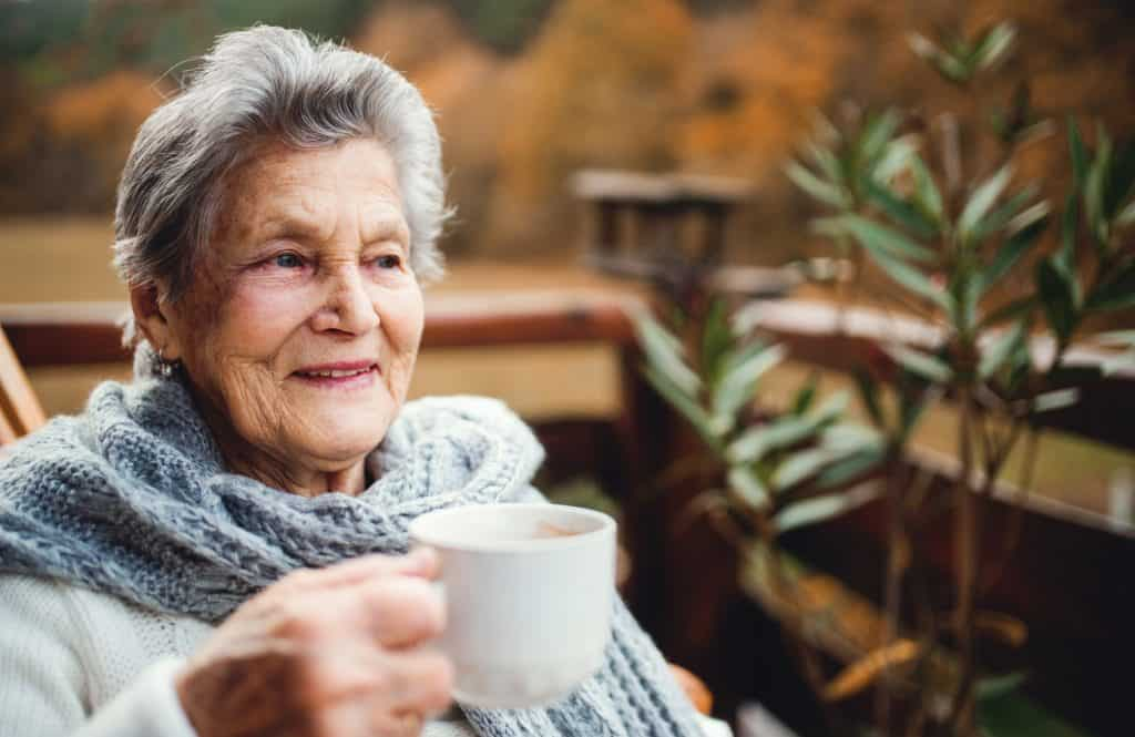 elderly lady warm and cosy with a cup of tea