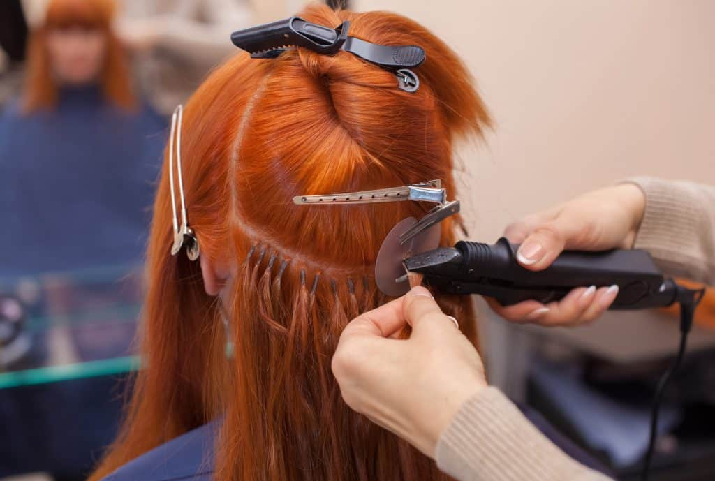 hair stylist doing hair extensions to a red-haired girl