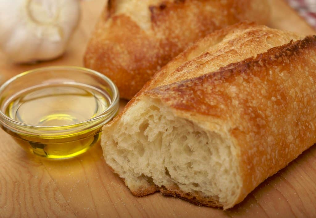 bread and olive oil on a wooden cutting board