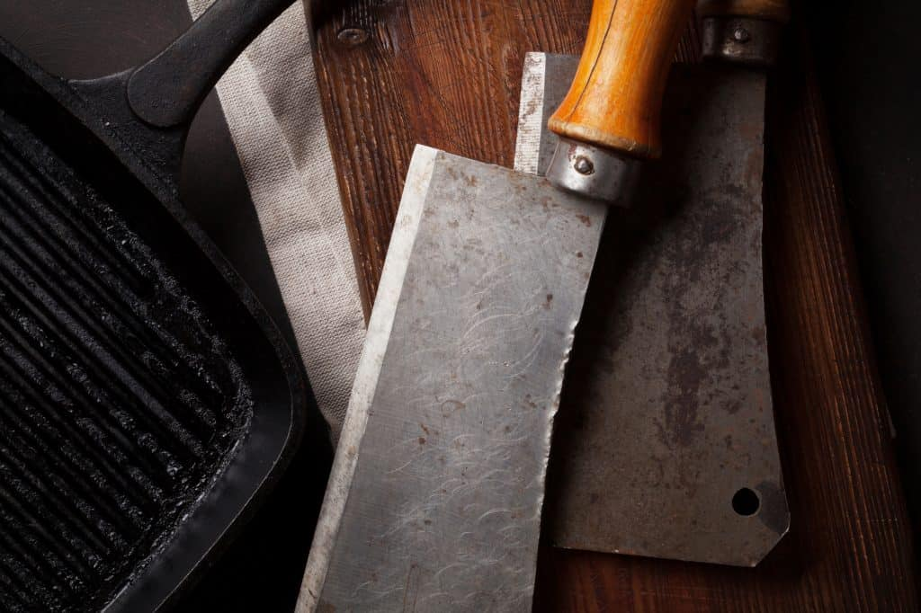 two old kitchen knives on a cutting board