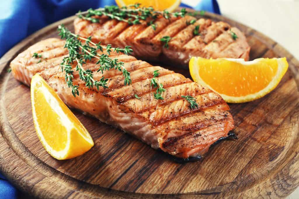 grilled salmon with orange slices on cutting board