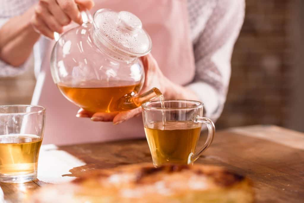 a woman pouring tea on a cup
