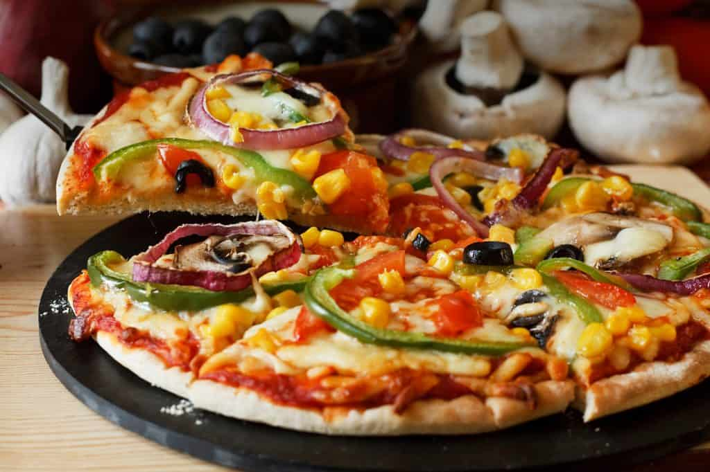 sliced vegan pizza with mushroom, tomatoes, onions, sweetcorn, and olives